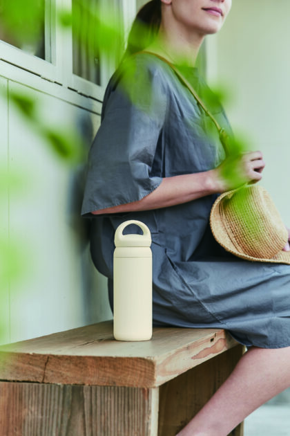 Woman sitting on bench next to a white day off thermos, day off kinto