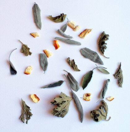 An assortment of dried herbs on a white board.