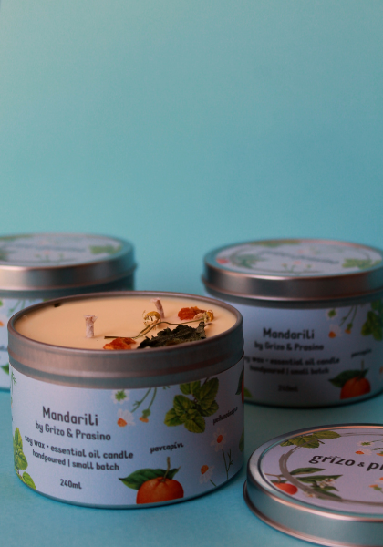 Three cans of candles. The background is light blue. The front candle is open and we can see the soy surface and the herbs on it.