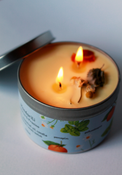 Close up photo of a lit candle. It has two wicks and on its surface you can find some raw dried herbs.