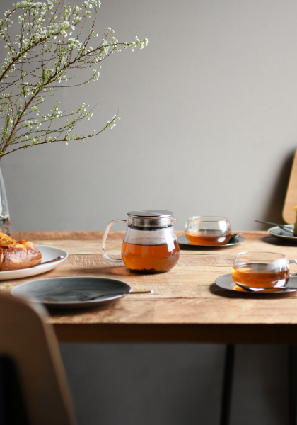 Breakfast table, with an assortment of plates and mugs on it, focused on the kinto one touch teapot in the middle.